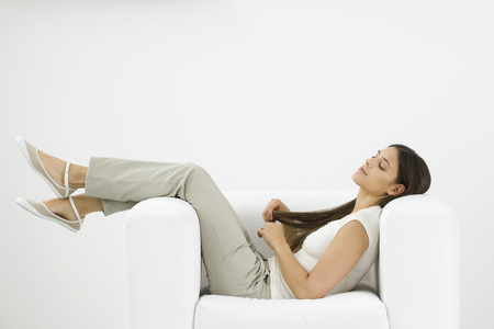 Woman reclining in armchair, playing with her hair