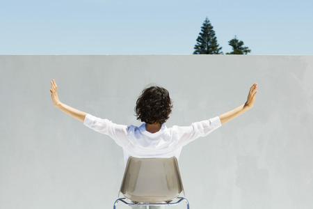 Woman seated facing wall, arms outstretched, rear view LANG_EVOIMAGES