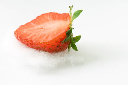 Fresh strawberry half on cotton, close-up LANG_EVOIMAGES