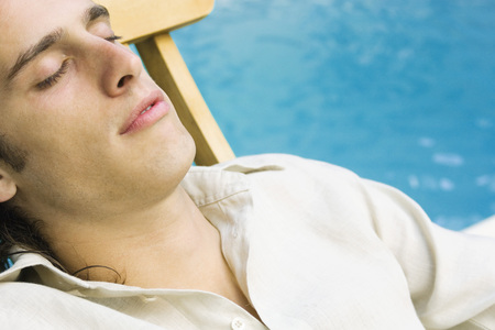 Man reclining in lounge chair beside pool, eyes closed, close-up