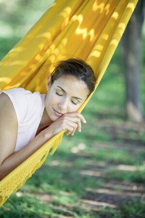 Woman resting in hammock, eyes closed