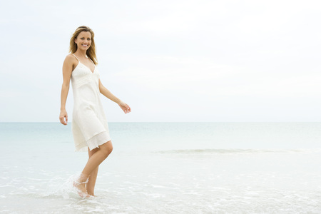 over the edge: Young woman in sundress walking in shallow water, smiling at camera LANG_EVOIMAGES