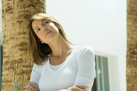 Woman with arms crossed, leaning against palm tree