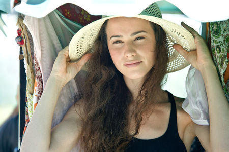 Young woman putting on straw hat, head and shoulders LANG_EVOIMAGES