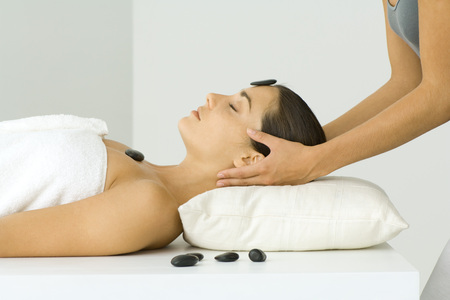 holistic view: Woman receiving massage and lastone treatment, close-up