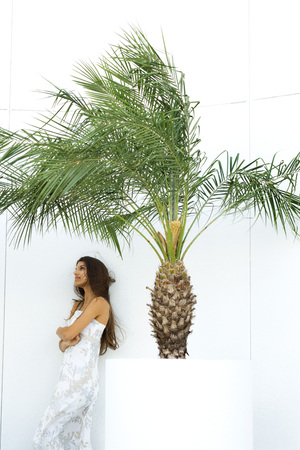 Teen girl in dress with arms crossed, standing next to palm tree in planter, looking away LANG_EVOIMAGES