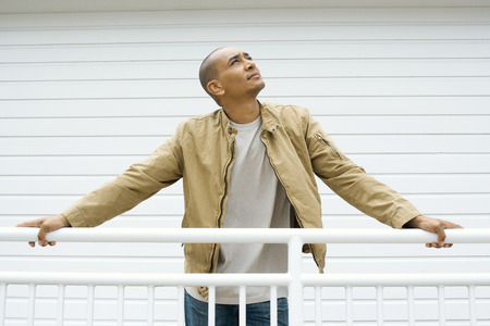 curiousness: Man holding on to railing, looking up