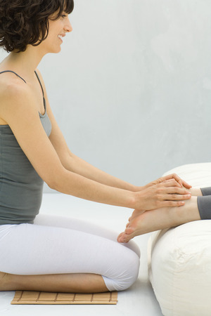 holistic view: Woman kneeling at foot of futon massaging another womans feet