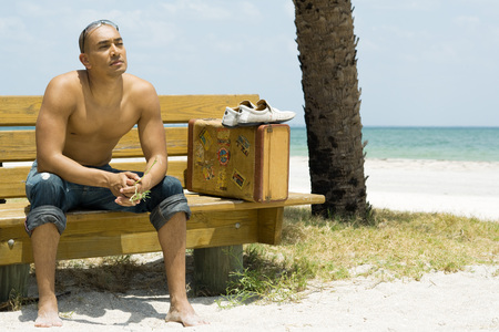 Man sitting on bench at the beach, suitcase beside him, looking away