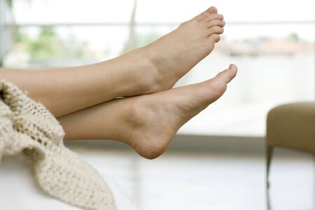 Womans bare feet, legs crossed at ankle LANG_EVOIMAGES