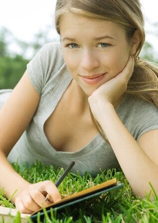 Young woman reclining in grass with notebook and pencil, portrait LANG_EVOIMAGES
