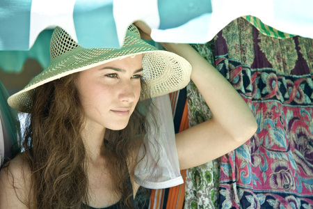 Young woman wearing straw hat, looking away LANG_EVOIMAGES