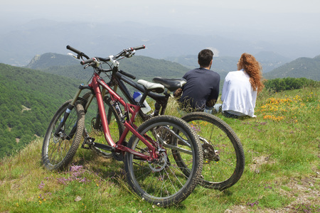 them: Couple sitting together on hill, looking at view, bicycles parked behind them