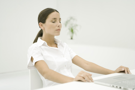 Woman sitting with laptop, eyes closed