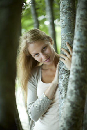 Woman leaning against tree trunk, portrait LANG_EVOIMAGES