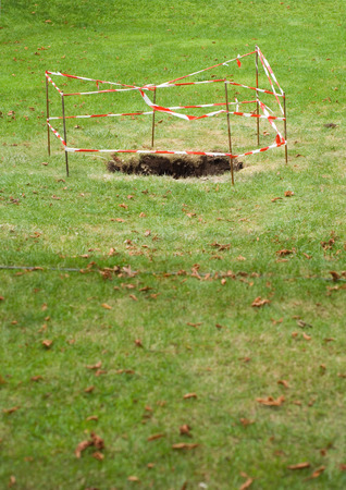 Hole in grass, roped off with barrier LANG_EVOIMAGES
