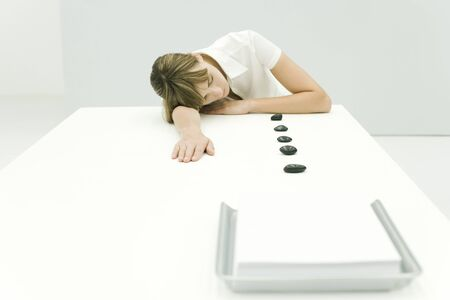 Woman resting head on table, lined up stones leading to stack of paper in tray