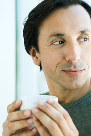 distractions: Mature man holding up cup, looking away, smiling LANG_EVOIMAGES