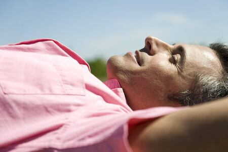 Man lying outdoors in sun with hands behind head LANG_EVOIMAGES