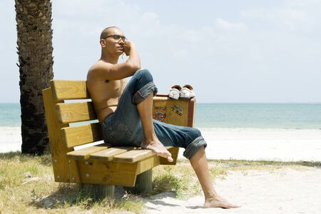 Man at the beach, sitting on bench beside suitcase, looking away