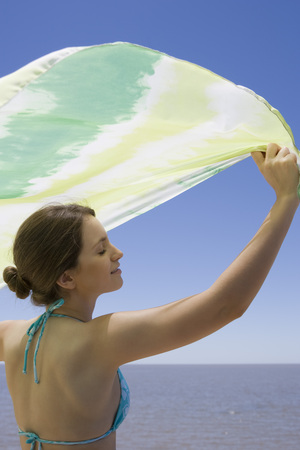 Young woman holding scarf in breeze, sea in background