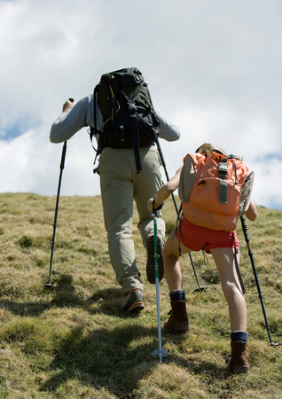 overcoming adversity: Hikers going uphill, rear view