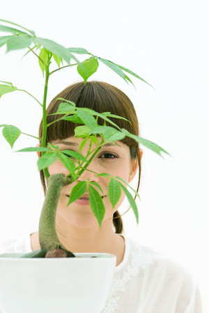 Woman looking through leaves of potted plant, smiling at camera LANG_EVOIMAGES