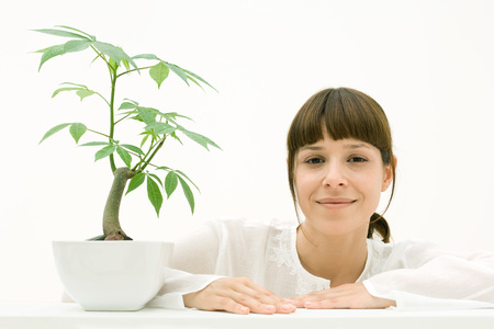 Woman sitting with potted plant, smiling at camera