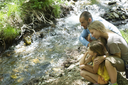 Family crouched together beside stream, looking at water