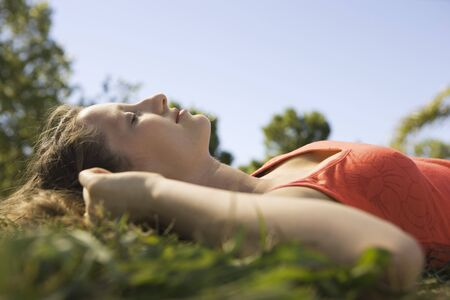 Young woman lying in grass with eyes closed