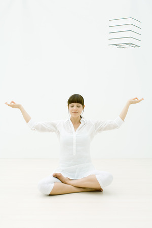 Woman sitting in lotus position with eyes closed, hands raised