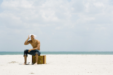 Man sitting on suitcase at the beach, covering head with handkerchief, looking up at sun