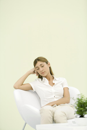 Woman sitting in chair, leaning against elbow, eyes closed LANG_EVOIMAGES