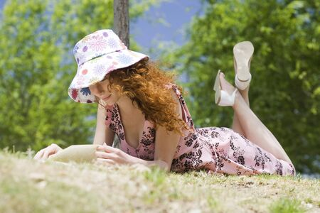 Young woman lying on stomach reading outdoors
