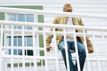 Man sitting on railing, smiling, looking up LANG_EVOIMAGES