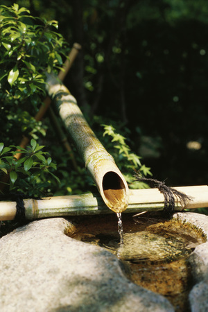 Water trickling from bamboo pipes into stone wash basin, Japan