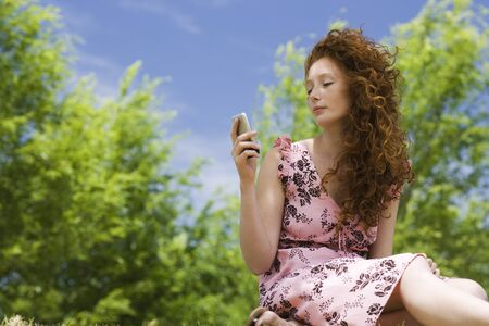 Young woman text messaging outdoors