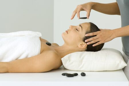 holistic view: Woman receiving lastone therapy, eyes closed