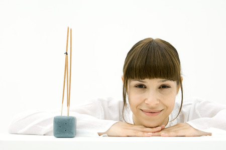 burned out: Woman resting head on arms beside incense, smiling at camera