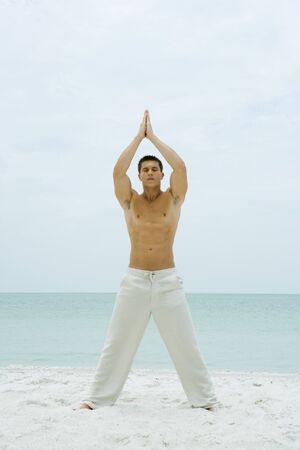 Bemannen Sie Stellung auf dem Strand und tun Sie Yoga, in voller Länge LANG_EVOIMAGES