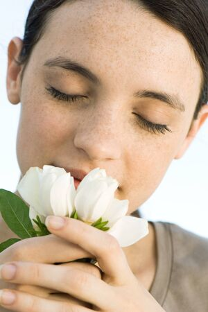 Young woman smelling flowers, close-up