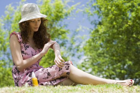 Young woman in sun hat sitting outdoors, applying sunscreen LANG_EVOIMAGES