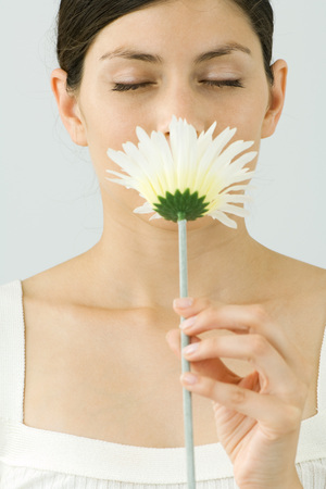Young woman smelling flower, eyes closed, portrait LANG_EVOIMAGES