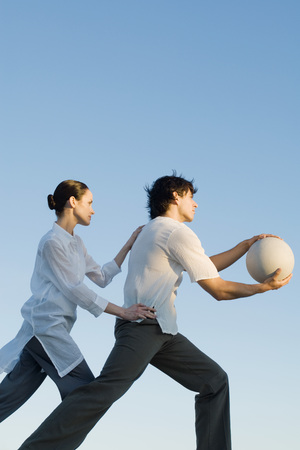 Man holding out ball, woman standing behind, hands on hip and shoulder LANG_EVOIMAGES