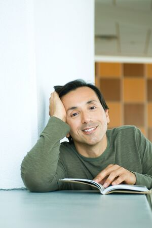 Man sitting with book, holding head, smiling at camera LANG_EVOIMAGES