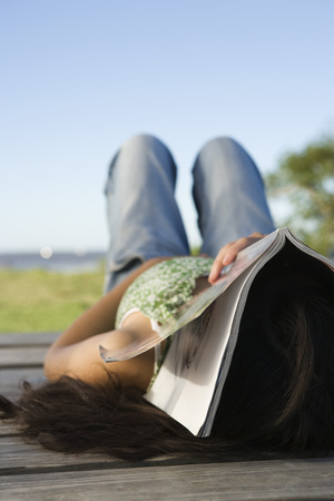 Woman lying on dock with magazine covering her face