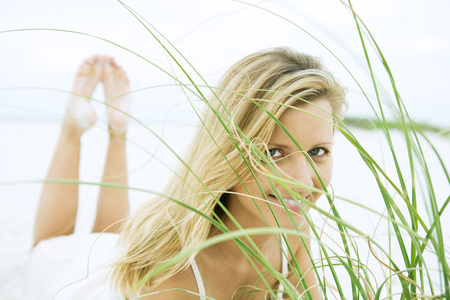 Woman lying on stomach, looking through grass, close-up LANG_EVOIMAGES