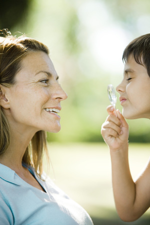 Mother and son, boy looking through magnifying glass, side view, close-up