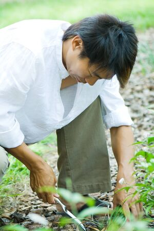 Man crouching outdoors, digging in garden with spade LANG_EVOIMAGES