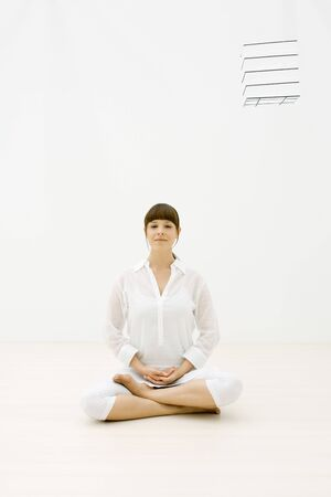 Woman sitting cross-legged, looking at camera, cube floating in midair